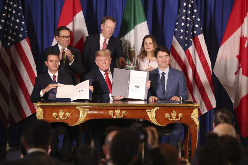FILE - In this Nov. 30, 2018 file photo, President Donald Trump, center, sits between Canada's Prime Minister Justin Trudeau, right, and Mexico's President Enrique Pena Nieto after they signed a new United States-Mexico-Canada Agreement that is replacing the NAFTA trade deal, during a ceremony at a hotel before the start of the G20 summit in Buenos Aires, Argentina. U.S. and Mexican unions have filed on Monday, May 10, 2021, the first labor complaint against Mexico under the U.S.-Mexico-Canada free trade pact.  (AP Photo/Martin Mejia, file)