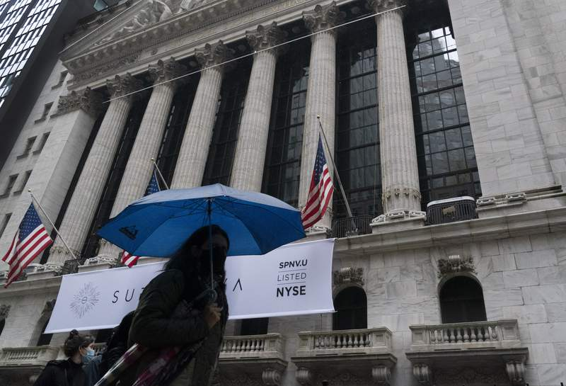 FILE - A woman with an umbrella passes the New York Stock Exchange, Monday, Oct. 26, 2020.  U.S. stocks are scuffling in early trading on Thursday, Nov. 12,  amid worries about worsening coronavirus counts across the country.   (AP Photo/Mark Lennihan, File)
