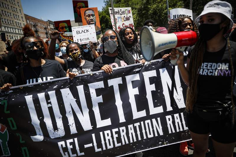 FILE: Protesters chant as they march after a Juneteenth rally at the Brooklyn Museum, Friday, June 19, 2020, in the Brooklyn borough of New York. Juneteenth commemorates when the last enslaved African Americans learned they were free 155 years ago. Now, with support growing for the racial justice movement, 2020 may be remembered as the year the holiday reached a new level of recognition. (AP Photo/John Minchillo)