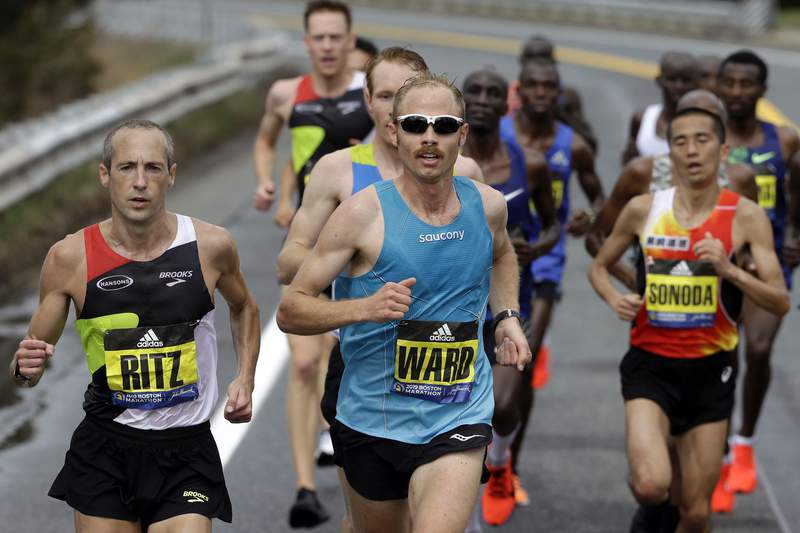 FILE - In this April 15, 2019, file photo, Jared Ward, center, of Mapleton, Utah, leads the pack in front as they run the course during the 123rd Boston Marathon in Natick, Mass. Footwear will be a the forefront at the U.S. Olympic marathon trials this weekend in Atlanta. No matter what time the marathoners turn in or how well they run, the they know their shoes will be the real headliner.(AP Photo/Steven Senne, File)