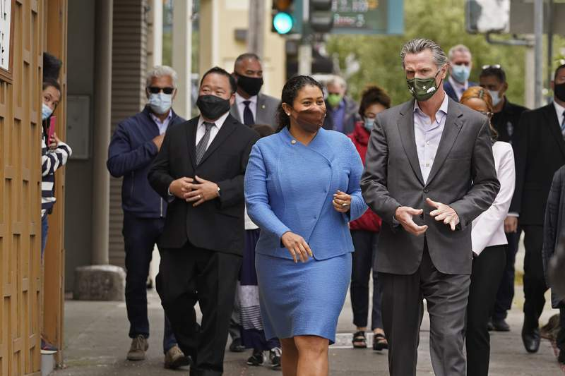 FILE - In this June 3, 2021 file photo California Gov. Gavin Newsom walks with San Francisco Mayor London Breed on Geary Street to a news conference outside Tommy's Mexican Restaurant in San Francisco. San Francisco will require proof of full vaccination against COVID-19 for a number of indoor activities such as visiting restaurants, bars and gyms. A city supervisor confirmed the new mandate shortly before Breed was scheduled to hold a news conference Thursday, Aug. 12, 2021. (AP Photo/Eric Risberg,File)