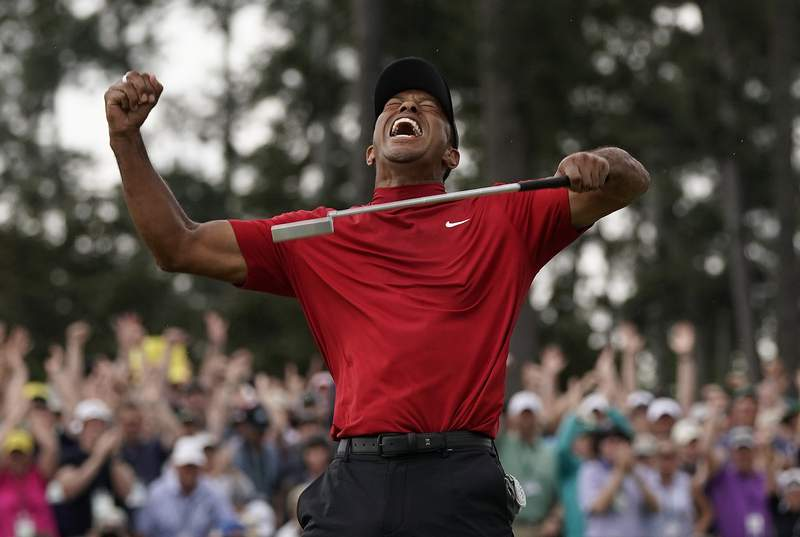 FILE - In this April 14, 2019, file photo, Tiger Woods reacts as he wins the Masters golf tournament in Augusta, Ga. The photo was part of a series of images by photographer David J. Phillip which won the Thomas V. diLustro best portfolio award for 2019 given out by the Associated Press Sports Editors during their annual winter meeting in St. Petersburg, Fla. (AP Photo/David J. Phillip, File)