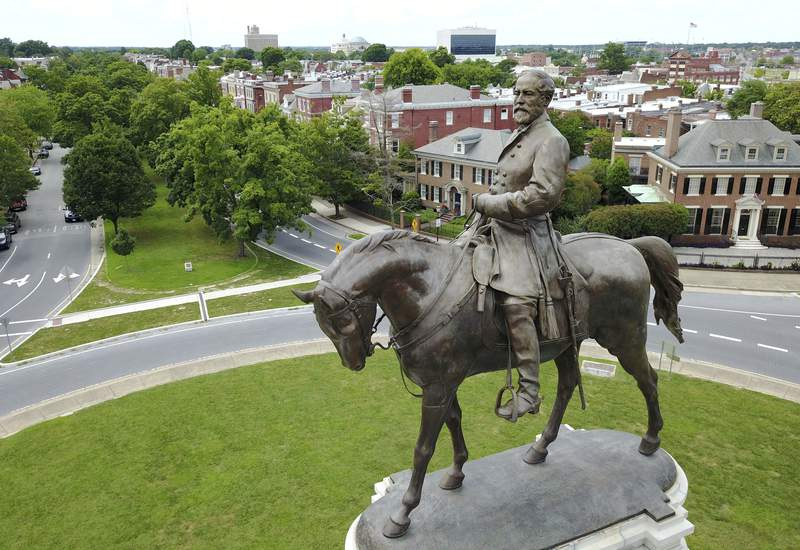FILE - This June 27, 2017, file photo, shows a statue of Confederate General Robert E. Lee in the middle of a traffic circle on Monument Avenue in Richmond, Va. Vestiges of the Civil War and Jim Crow segregation are coming down across the Old Confederacy as part of a national reckoning on race and white supremacy. A diversifying Democratic Party hopes the changes in symbols are part of a more fundamental shift in a region that dominated by Republicans for a generation  and white conservative Democrats a century before that. (AP Photo/Steve Helber, File)