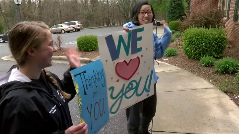 Local students hold up signs outside of Lynchburg retirement home