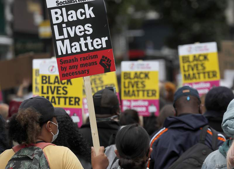 """FILE - In this Sunday, Aug. 30, 2020 file photo, Black Lives Matter protesters hold posters as they march through Notting Hill during the """"Million People March"""" through central London. A body of experts that advises the United Nations on human rights concerns has slammed a widely criticized British government-backed report that concluded there was no systemic racism in the country. The U.N. Working Group of Experts on People of African Descent said Monday April 19, 2021 that it found it stunning that the report repackages racist tropes and stereotypes into fact and urged the British government to reject its findings. (AP Photo/Frank Augstein, File)"""