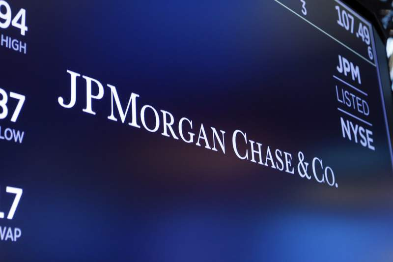 FILE - In this Aug. 16, 2019, file photo, the logo for JPMorgan Chase & Co. appears above a trading post on the floor of the New York Stock Exchange in New York. A number of JPMorgan Chase traders have been sent home after employees tested positive for COVID-19, less than a week into the banks push to start bringing its workers back into the office. A bank spokesman said Tuesday, Sept. 25, 2020, that JPMorgan Chase has been managing individual positive cases over the last few months. (AP Photo/Richard Drew, File)