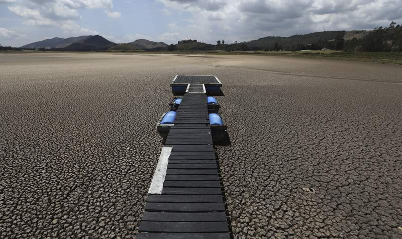FILE - In this Wednesday, Feb. 17, 2021 file photo, a floating dock sits on the lakebed of the Suesca lagoon, in Suesca, Colombia. The lagoon, a popular tourist destination near Bogota that has no tributaries and depends on rain runoff, has radically decreased its water surface due to years of severe droughts in the area and the deforestation and erosion of its surroundings. (AP Photo/Fernando Vergara, File)