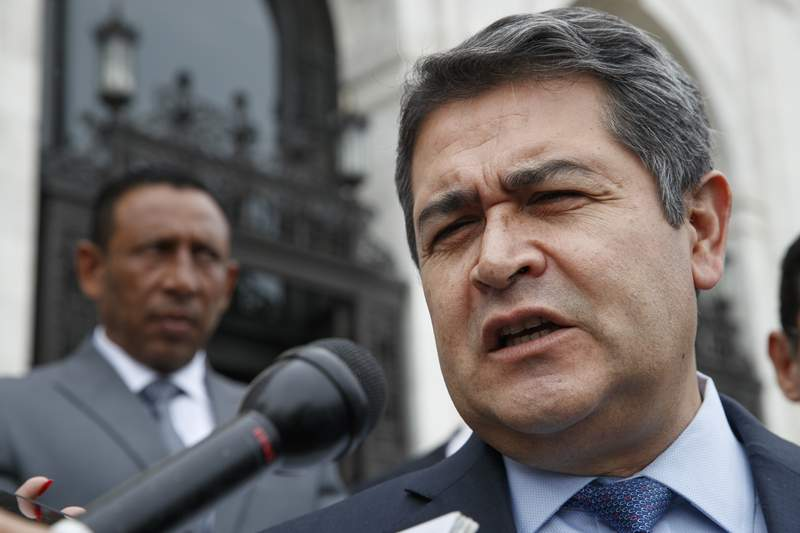 FILE - In this Aug. 13, 2019 file photo, Honduran President Juan Orlando Hernandez answers questions from the Associated Press, as he leaves a meeting at the Organization of American States, in Washington. U.S. prosecutors said on Tuesday, March 3, 2020, that Hernandez met with an Honduran drug dealer in 2013 and agreed to facilitate the use of Honduran armed forces personnel as security for the dealers drug trafficking activities. In 2013, Hernandez was a congressman. He was elected president at the end of that year. (AP Photo/Jacquelyn Martin, File)