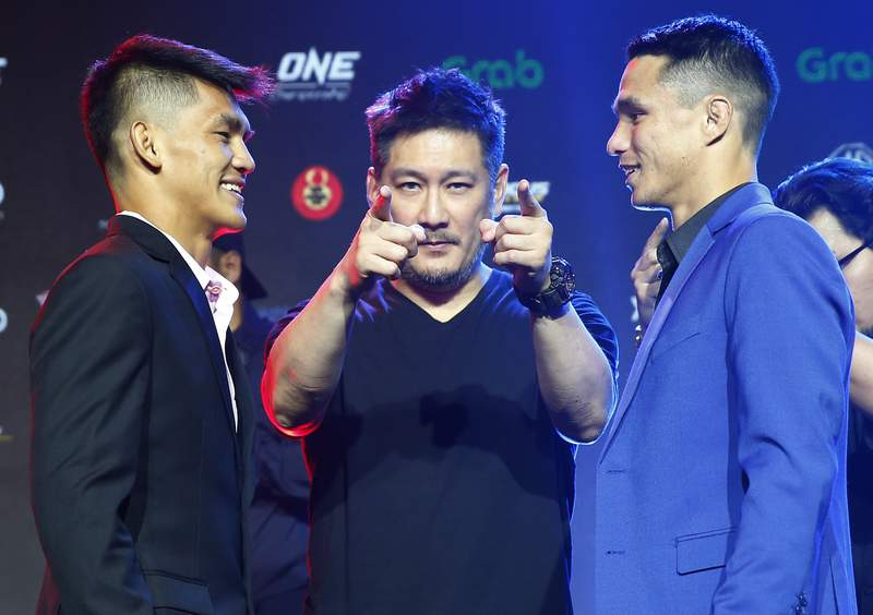 FILE - In this Tuesday, July 30, 2019 file photo, Chatri Sityodtong, Chair and CEO of ONE Championship, center, gestures as Reece McLaren, right, of Australia and Danny Kingad, left, of the Philippines face off during the media presentation for this Friday's ONE Championship mixed martial arts fight dubbed: Dawn of Heroes, in suburban Pasay city south of Manila, Philippines. One Championship definitely will return to action this summer during this unprecedented public health crisis, Chatri Sityodtong told The Associated Press on Wednesday June 10, 2020, but the promotion has not finalized a date or location for its first fights. (AP Photo/Bullit Marquez, File)