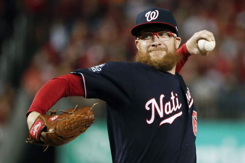 FILE - In this Oct. 27, 2019, file photo, Washington Nationals relief pitcher Sean Doolittle throws during the seventh inning of Game 5 of the baseball World Series against the Houston Astros, in Washington. The Nationals told their minor leaguers on Monday, June 1, 2020, they will receive their full weekly stipends of $400 at least through June after Washington reliever Sean Doolittle tweeted that the teams major league players would cover a planned cut in those payments.(AP Photo/Jeff Roberson, File)