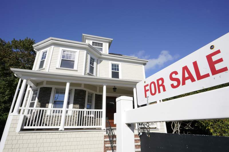 FILE - A for sale sign stands in front of a house, Tuesday, Oct. 6, 2020, in Westwood, Mass.   U.S. long-term mortgage rates dropped this week to a record low for the 16th time in 2020, reflecting an economy hard hit by the coronavirus pandemic. Mortgage giant Freddie Mac said Thursday, Dec. 24,  that the average rate on the benchmark 30-year fixed-rate home loan slipped to 2.66% from 2.67% last week.   (AP Photo/Steven Senne, File)