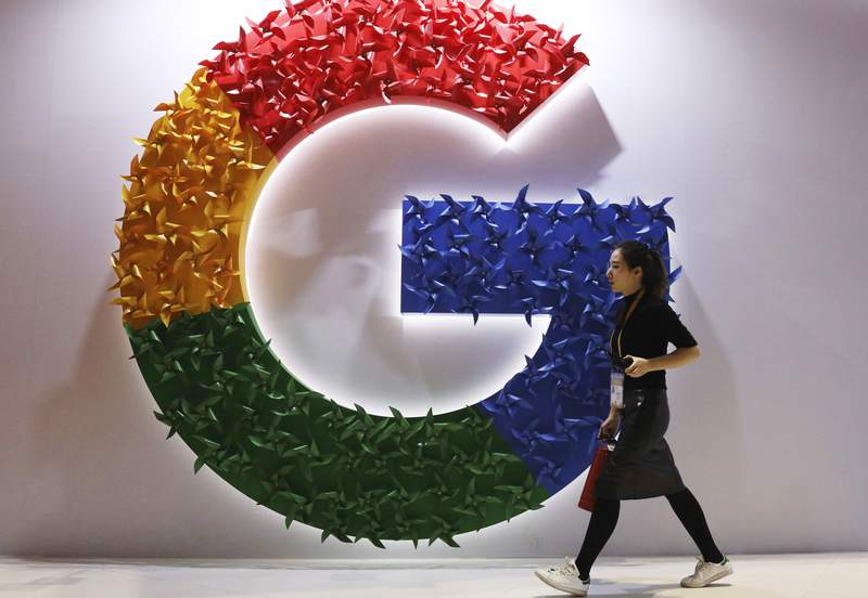 FILE - In this Monday, Nov. 5, 2018 file photo, a woman walks past the logo for Google at the China International Import Expo in Shanghai. Google said Thursday June 24, 2021, it's delaying plans to phase out Chrome browser technology that tracks users for ad purposes because it needs more time to develop a replacement system. (AP Photo/Ng Han Guan, File)