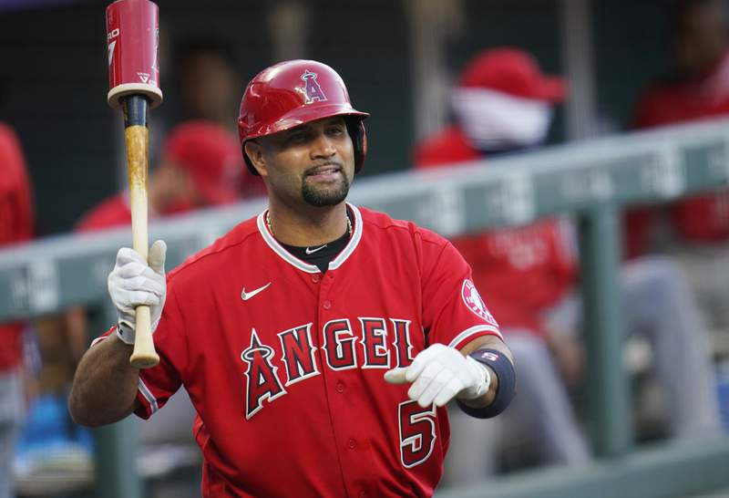 FILE - In this Sept. 12, 2020, file photo, Los Angeles Angels designated hitter Albert Pujols waves to players in the Colorado Rockies dugout in the second inning of a baseball game in Denver. Pujols wife apparently disclosed that the Angels slugger will retire after the upcoming season, although she later amended her social media post to be less definitive. (AP Photo/David Zalubowski, File)