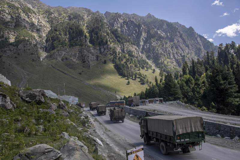 FILE - In this Sept. 9, 2020, file photo, an Indian army convoy moves on the Srinagar- Ladakh highway at Gagangeer, northeast of Srinagar, Indian-controlled Kashmir. The Indian military said it apprehended a Chinese soldier Monday, Oct. 19, in the remote Ladakh region, where the two countries are locked in a monthslong military standoff along their disputed border. (AP Photo/ Dar Yasin, File)