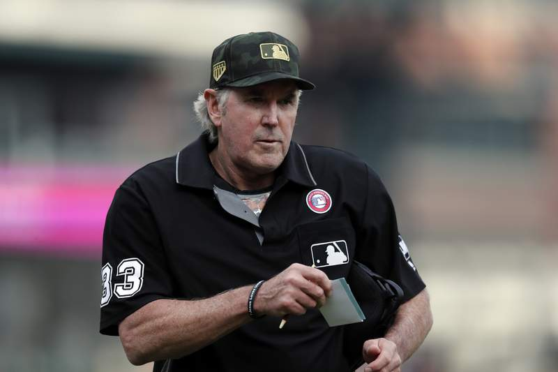FILE - In this May 18, 2019, file photo, home plate umpire Mike Winters looks on during the eighth inning of a baseball game between the Detroit Tigers and the Oakland Athletics in Detroit. After more than three decades of hard work as a big league umpire, Winters is retiring. (AP Photo/Carlos Osorio, File)