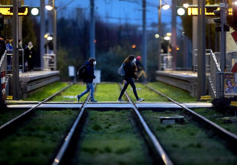 Pupils wearing face masks cross the rails to catch a subway in Frankfurt, Germany, Monday, Nov. 2, 2020. A one month long partial lockdown becomes effective in Germany on Monday. (AP Photo/Michael Probst)