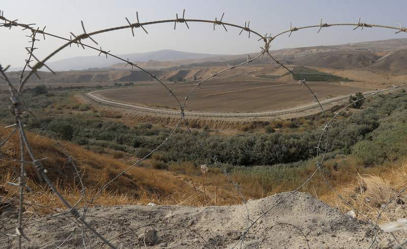 FILE - In this Nov. 13, 2019, file photo, a portion of the Israeli-Jordanian border is viewed through a barbed wire fence from Baqoura, in the Jordan Valley. Jordans Foreign Ministry on Thursday, April 30, 2020 announced that Israeli farmers will no longer be allowed to work their fields in an enclave of southern Jordan, ending a more than 25-year arrangement meant to shore up a historic peace agreement. (AP Photo/Raad Adayleh, File)