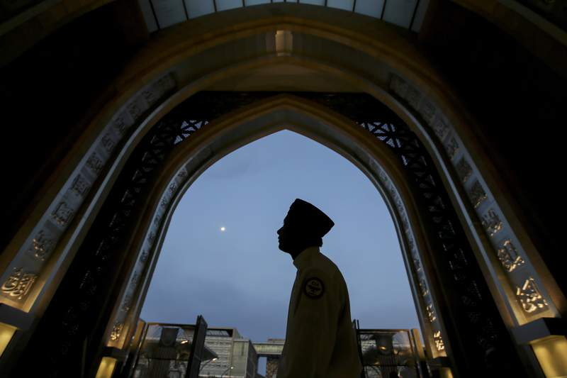 FILE - In this May 16, 2019, file photo, a worshiper arrives at a mosque for Iftar during the holy Islamic month of Ramadan in Kuala Lumpur, Malaysia. A Malaysian court ruled Wednesday, March 10, 2021, that non-Muslims can use the word Allah to refer to God, in a major decision in a divisive issue for religious freedom in the Muslim-majority country. (AP Photo/Annice Lyn, File)