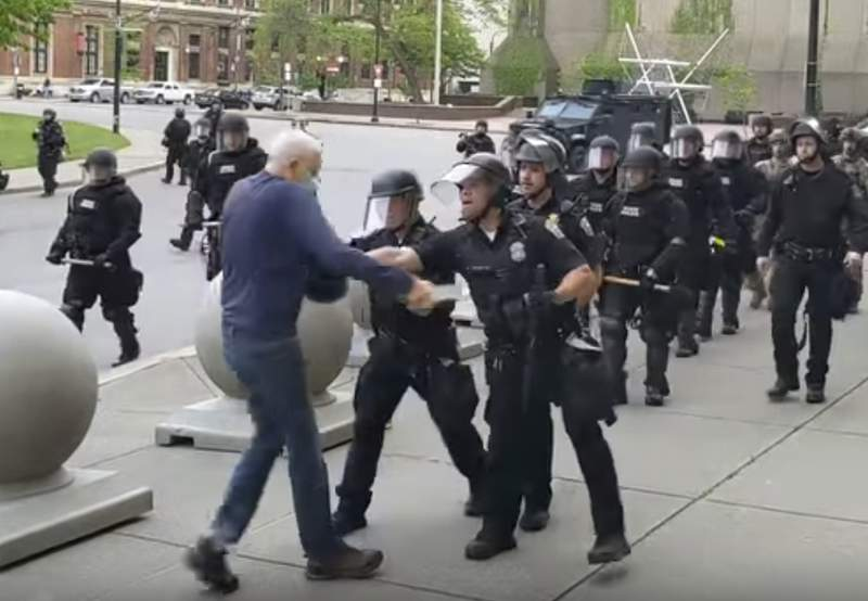 In this image from video provided by WBFO, a Buffalo police officer appears to shove a man who walked up to police Thursday, June 4, 2020, in Buffalo, N.Y. Video from WBFO shows the man appearing to hit his head on the pavement, with blood leaking out as officers walk past to clear Niagara Square. Buffalo police initially said in a statement that a person was injured when he tripped & fell, WIVB-TV reported, but Capt. Jeff Rinaldo later told the TV station that an internal affairs investigation was opened. Police Commissioner Byron Lockwood suspended two officers late Thursday, the mayors statement said. (Mike Desmond/WBFO via AP)