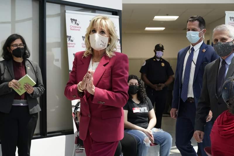 First lady Jill Biden gestures as she and Dr. Anthony Fauci, director of the National Institute of Allergy and Infectious Diseases, far right, tour a COVID-19 vaccination site Thursday, May 20, 2021, at Children's Hospital in Washington. (AP Photo/Jacquelyn Martin)