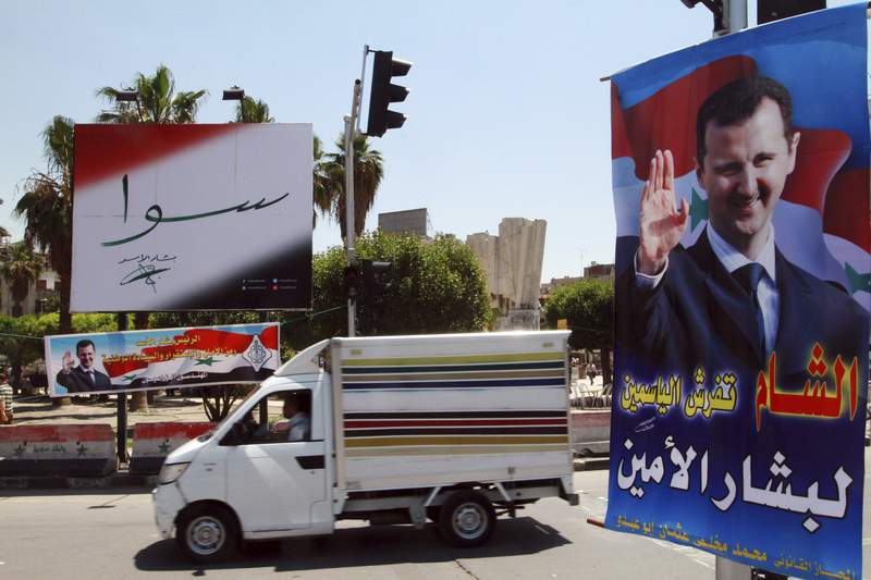 "FILE - In this May 12, 2014 file photo, campaign posters for the upcoming presidential election adorn a street in Damascus, Syria. On Monday April 26, 2021, the Paris-based Syrian Network for Human Rights called on the international community to reject presidential elections in the war-torn country scheduled for May, describing them as a sham because they will take place under President Bashar Assad, who is implicated in war crimes. Arabic on the poster, right, reads, ""Damascus spreads flowers for the loyal Bashar."" The banner reads, ""Together with Bashar Assad."" (AP Photo, File)"