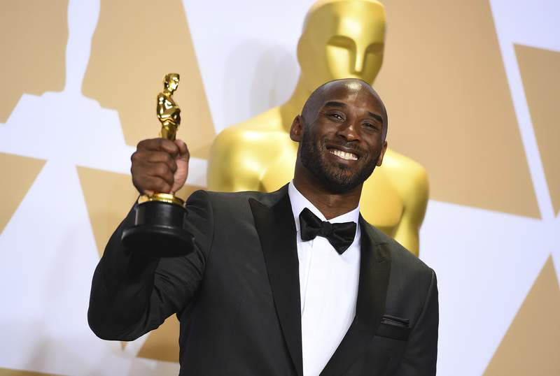 """FILE - This March 4, 2018 file photo shows Kobe Bryant, winner of the award for best animated short for """"Dear Basketball"""",  at the Oscars in Los Angeles. Bryant, a five-time NBA champion and a two-time Olympic gold medalist, died in a helicopter crash in California on Sunday, Jan. 26, 2020. He was 41. (Photo by Jordan Strauss/Invision/AP, File)"""
