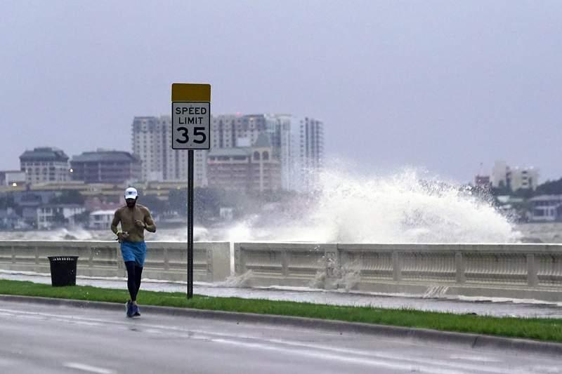 Un corredor pasa por el Bulevar Bayshore en Tampa, Florida, mientras una ola rompe sobre el muelle tras el paso de la tormenta tropical Elsa, el mircoles 7 de julio de 2021. (AP foto/John Raoux)