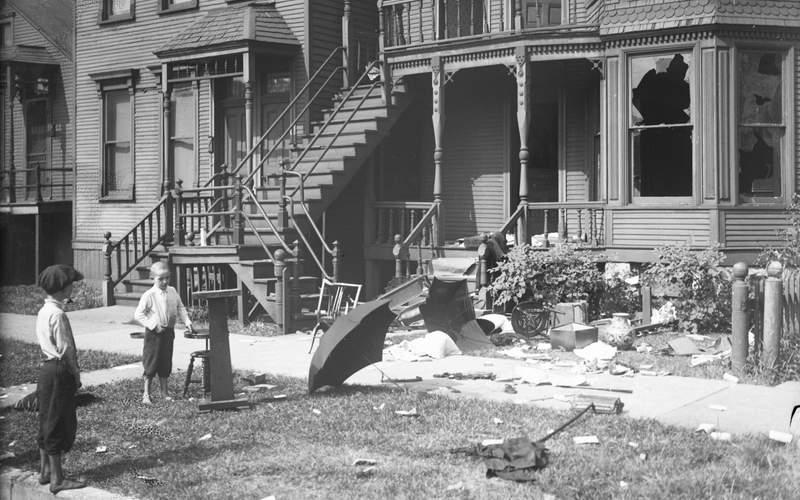 """A view of two young boys outside a home with broken windows and debris in the front yard, which had been vandalized during a race riot in Chicago, in the summer of 1919. The riot reportedly began following an incident at an informally segregated Chicago beach where a young Black boy drowned after a white man threw rocks at him -- resulting in a week-long riot with dozens of deaths and more than 1,000 left homeless. The events in Chicago were just one of a number of violent confrontations, grouped as the """"Red Summer"""" events that occurred that year in the United States as a result of post-war economics, labor unrest, and racial tensions stoked by white supremacist groups."""