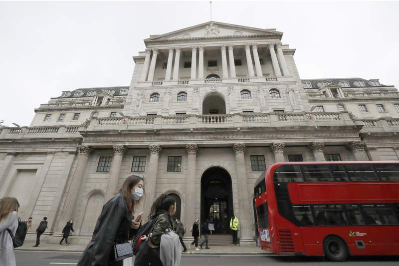 FILE - In this Wednesday, March 11, 2020 file photo, pedestrians wearing face masks pass the Bank of England in London.  The Bank of England has kept its main interest rate at the record low of 0.1%. In a statement Thursday, June 24, 2021 accompanying its decision, the banks rate-setting Monetary Policy Committee voted unanimously to keep borrowing rates unchanged. (AP Photo/Matt Dunham, File)