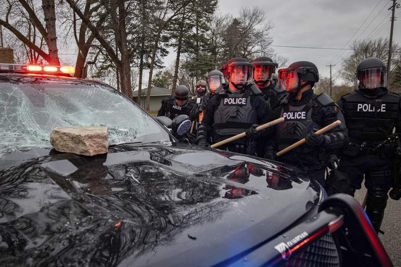 Police stand near a police cruiser after a rock was thrown at it in protest, Sunday, April 11, 2021, in Brooklyn Center, Minn. The family of Daunte Wright, 20, told a crowd that he was shot by police Sunday before getting back into his car and driving away, then crashing the vehicle several blocks away. The family said Wright was later pronounced dead. (AP Photo/Christian Monterrosa)