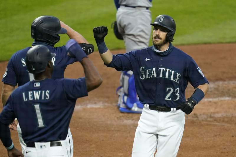 Seattle Mariners' Austin Nola (23) is greeted at home on his three-run home run by Kyle Lewis (1) and Kyle Seager during the third inning of a baseball game against the Los Angeles Dodgers on Wednesday, Aug. 19, 2020, in Seattle. (AP Photo/Elaine Thompson)