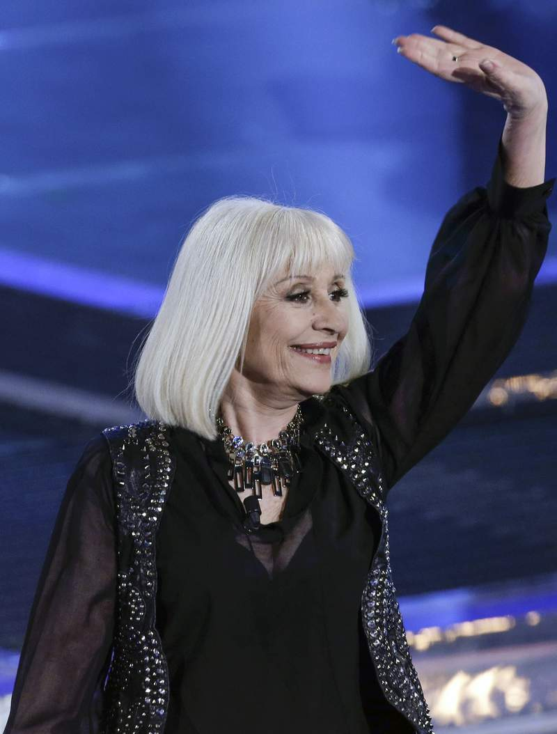 """Italian singer Raffaella Carra' waves during the Italian State RAI TV program """"The Voice of Italy"""", in Milan, Italy, Wednesday, May 28, 2014. Italian Rai state TV says Raffaella Carra', for decades one of Rai's most popular entertainers, has died. It quoted the star's family as saying she died on Monday after a long illness but in keeping with her wishes no details were being released. Carra', 78, with her energetic prancing on stage and forceful singing voice, was a beloved, longtime staple in the early heyday decades of the state broadcaster. (AP Photo/Luca Bruno)"""