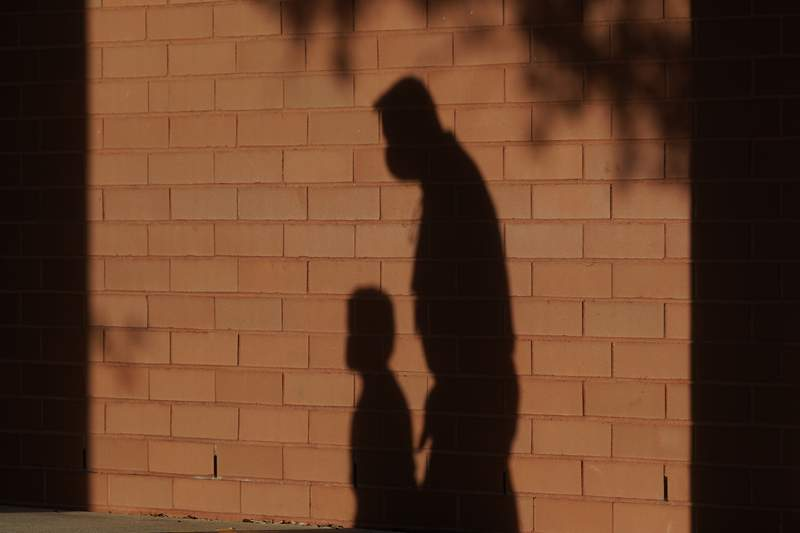 FILE - In this Friday, Oct. 9, 2020 file photo, the shadows of a school employee escorting a student are cast on the wall as they walk to a classroom on the first day of class at an elementary School in Davie, Fla. On Thursday, Jan. 14, 2021, top officials overseeing child welfare at the Department of Health and Human Services say theyve seen no solid evidence to bear out warnings that serious forms of child abuse would surge during the coronavirus pandemic. (AP Photo/Wilfredo Lee)