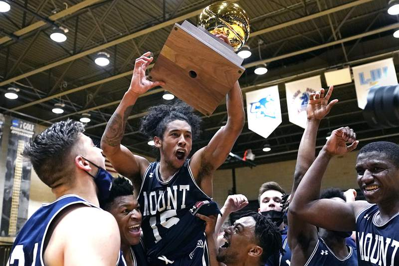 Mount St. Mary's guard Damian Chong Qui (15) hoists the trophy as he celebrates with teammates after their win in an NCAA college basketball game for the Northeast Conference men's tournament championship against Bryant, Tuesday, March 9, 2021, in Smithfield, R.I. (AP Photo/Charles Krupa)
