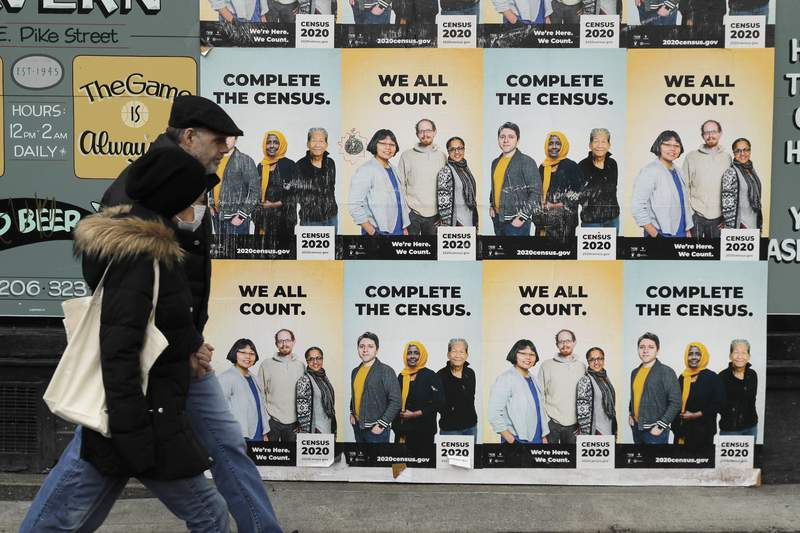 FILE - In this Wednesday, April 1, 2020 file photo, People walk past posters encouraging participation in the 2020 Census in Seattle's Capitol Hill neighborhood. From McKenzie County, North Dakota to St. Johns County Florida, the growth in the number of people who identified as multiracial on 2020 census responses soared over the last decade, rising from under 3% to more than 10% of the U.S. population from 2010 and 2020.(AP Photo/Ted S. Warren, File)