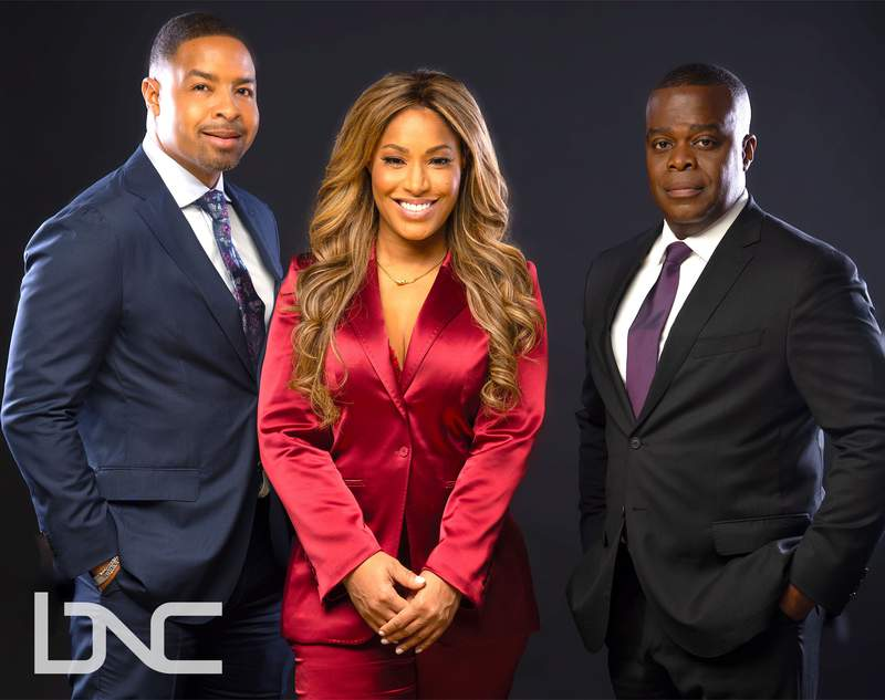 This image released by BNC shows Mike Hill, left, and Sharon Reed posing with Black News Channel president & CEO Princell Hair. The Black News Channel, nearly invisible upon its launch last year, is revamping to take on a new look starting Monday. It is adding a four-hour morning show with Hill and Reed and will be emphasizing commentary and analytical news coverage moving forward. (BNC via AP)