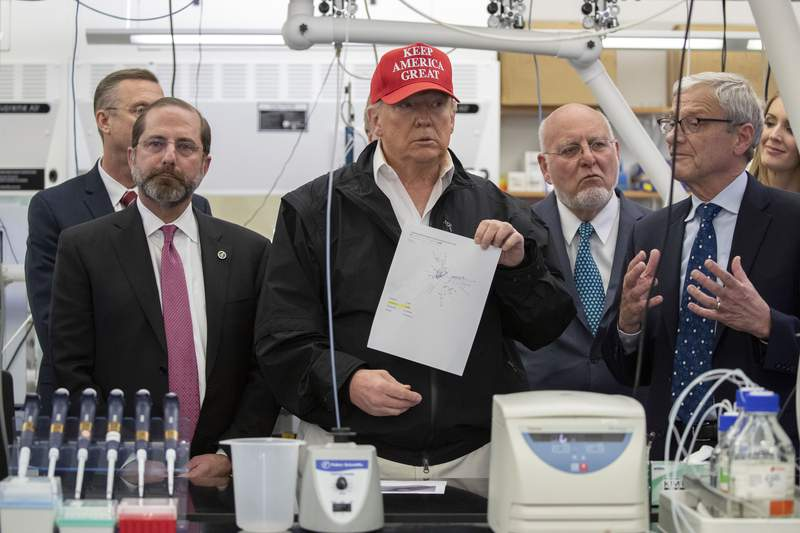 President Donald Trump holds up a picture as he listens during a meeting with Health and Human Services Secretary Alex Azar, left, Associate Director for Laboratory Science and Safety Steve Monroe, and Centers for Disease Control and Prevention Director Dr. Robert Redfield, about the coronavirus at the Centers for Disease Control and Prevention, Friday, March 6, 2020 in Atlanta. (AP Photo/Alex Brandon)
