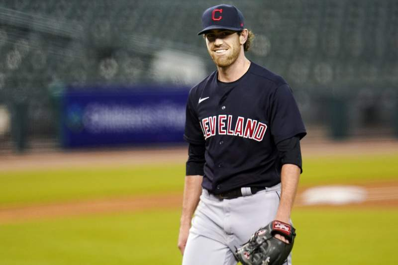 FILE - In this Sept. 17, 2020, file photo, Cleveland Indians pitcher Shane Bieber smiles as he walks to the dugout in the fourth inning of a baseball game against the Detroit Tigers in Detroit. Bieber has reported to training camp with the Cleveland Indians after recovering from COVID-19. The right-hander took part in drills on Saturday, Feb. 20, 2021, a day before the Indians hold their first full-squad workout in Goodyear, Ariz.  (AP Photo/Paul Sancya, File)