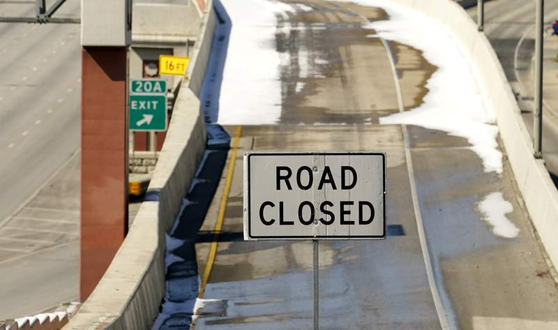 A sign blocks an on ramp to Interstate 410, Friday, Feb. 19, 2021, in San Antonio. Many roads, highways and interstates remain closed to to icy conditions. (AP Photo/Eric Gay)