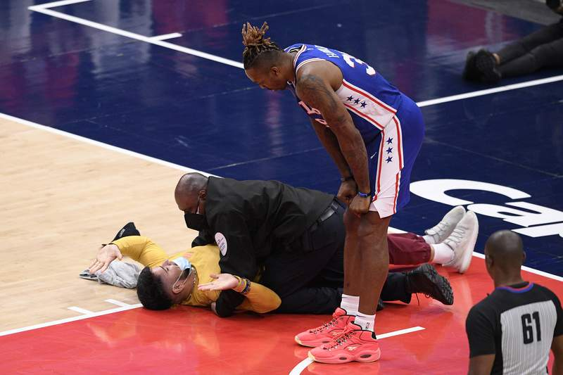 Philadelphia 76ers center Dwight Howard (39) watches as a fan who ran onto the court is restrained by security personnel during the second half of Game 4 in a first-round NBA basketball playoff series against the Washington Wizards, Monday, May 31, 2021, in Washington. (AP Photo/Nick Wass)