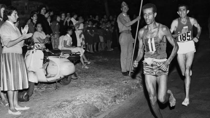 Abebe Bikila of Ethiopia, running barefoot, draws away from Abdesselem Rhadi of Morocco near the finish of the marathon at the 1960 Rome Olympics. He went on to win with a new Olympic record time of 2 hours 15 minutes 16 seconds. (Photo by Central Press)