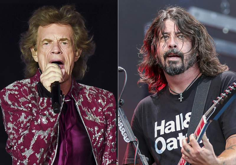 Musician Mick Jagger of The Rolling Stones performs in East Rutherford, N.J. on Aug. 1, 2019, left, Dave Grohl of the Foo Fighters performs at Pilgrimage Music and Cultural Festival in Franklin, Tenn. on Sept. 22, 2019. Jagger and Grohl have teamed up for a hard-rock pandemic anthem called Eazy Sleazy. The duo recorded the song in different studio locations and the lyrics mention prison walls, virtual premieres, numbers that are grim and Zoom calls. (AP Photo)