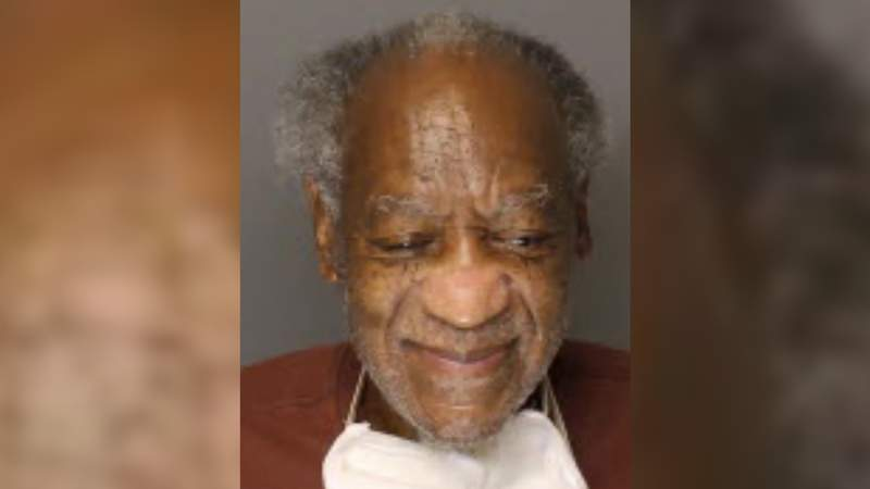A newly released prison mug shot shows Bill Cosby smiling with a disposable mask hanging off his face.