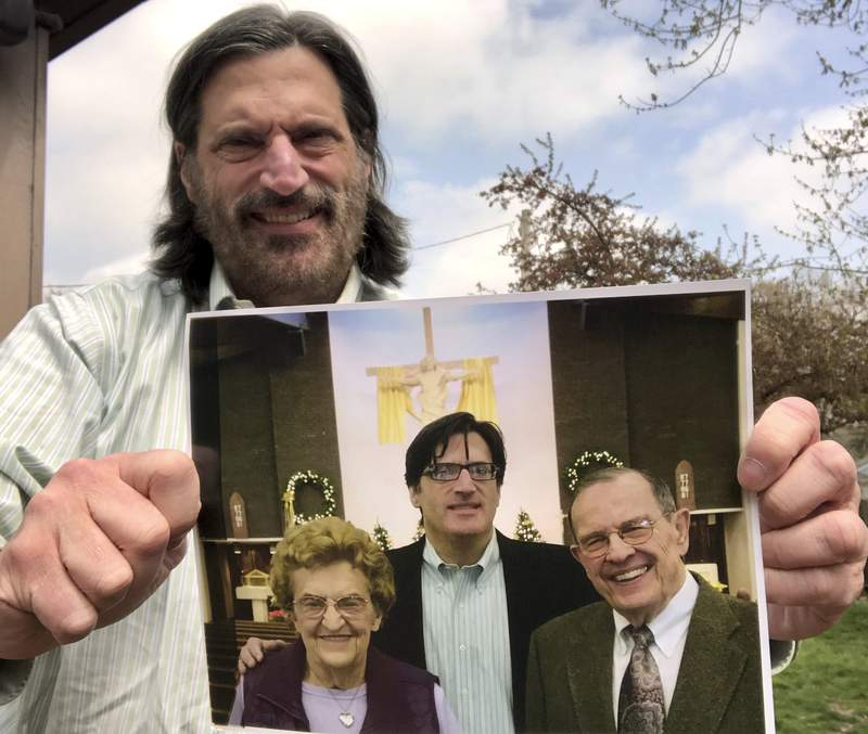 In this April 16, 2020, photo, John OConnor, a reporter for The Associated Press in Springfield, Ill., holds a photo of his parents, Jack and Shirley OConnor, and him at their 60th wedding anniversary celebration on Jan. 2, 2016. Jack and Shirley OConnor, both 90, live in the house they bought in 1959 in Freeport, Ill. OConnor says he and his siblings have focused on keeping their parents healthy during the coronavirus pandemic, which has kept the couple home, but hasnt stopped the prayerful life they lead. (AP Photo/John OConnor)