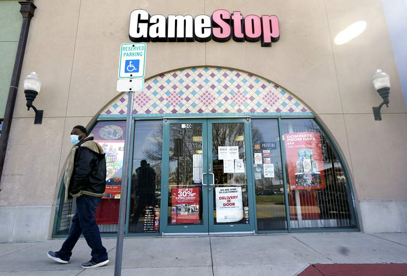 FILE - In this Jan. 28, 2021 file photo, a pedestrian passes a GameStop storefront in Dallas. GameStop shares jumped around 12% in premarket trading Monday, March 8 after the video game retailer appointed a committee it said would aim to transform GameStop into a technology business.  (AP Photo/LM Otero, File)