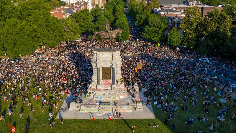 """Image has been edited to remove profanity. In this photo taken with a drone, a large group of protesters gather around the statue of Confederate General Robert E. Lee on Monument Avenue near downtown Tuesday, June 2, 2020, in Richmond, Va. The crowd protesting police brutality chanted """"Tear it down."""""""