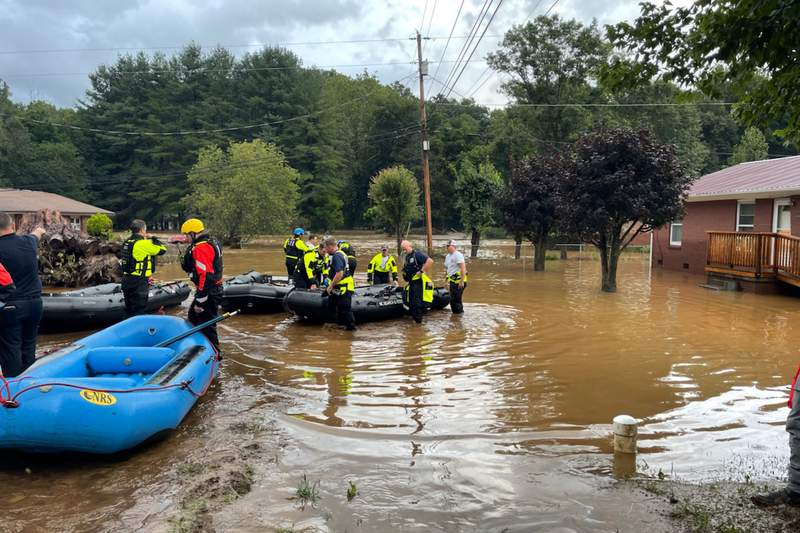 In this image provided by New Hanover County Fire Rescue, members of North Carolinas Task Force 11, based in New Hanover County, are shown during rescue efforts in Canton, N.C, on Tuesday, Aug. 17, 2021. Authorities said that dozens of water rescues were performed after the remnants of Tropical Storm Fred dumped rain on the mountains of North Carolina. (New Hanover County Fire Rescue via AP)