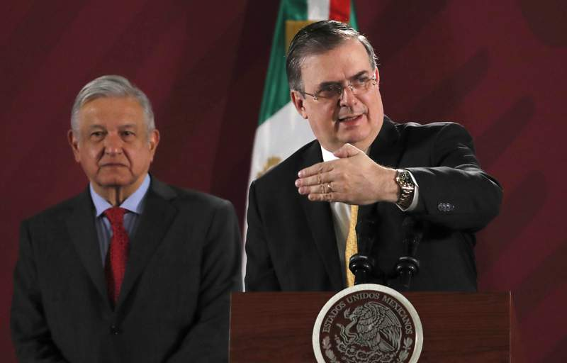 FILE - In this Nov. 12, 2019 file photo, Mexican Foreign Minister Marcelo Ebrard answers questions from the press as President Andres Manuel Lopez Obrador stands behind during the president's daily morning press conference at the National Palace, in Mexico City. A gathering of leaders from Latin America and the Caribbean in Mexico City on Saturday, Sept. 17, 2021,  is the latest sign of Mexico flexing its diplomatic muscle as it looks to assert itself as the new mediator between the region and the United States.  (AP Photo/Marco Ugarte, File)