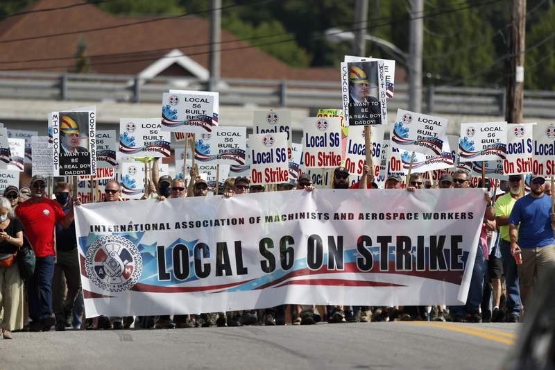 FILE - Striking Bath Iron Works shipbuilders march in solidarity, Saturday, July 25, 2020, in Bath, Maine.  The union representing striking production workers says a tentative agreement was reached with Navy shipbuilder Bath Iron Works to end a strike that stretched for more than a month during a global pandemic. The agreement announced on Saturday, Aug. 8,  will be put forth to the 4,300 members of Machinists Local S6 for approval. (AP Photo/Robert F. Bukaty, File)