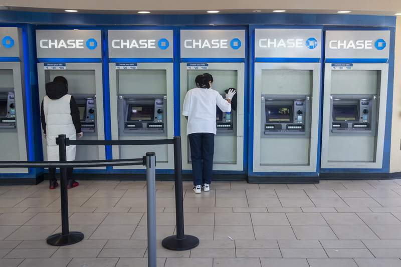 FILE - In this March 24, 2020 file photo, a Chase bank employee, right, disinfects the branches ATMs to fend off coronavirus as a customer uses another in the Flushing neighborhood of the Queens borough of New York. The U.S. banking industrys second quarter profits fell by 70% from a year ago, the FDIC said Tuesday, Aug. 25 as low interest rates and the economic turmoil of the COVID-19 pandemic weighed heavily on big and small banks alike. (AP Photo/Mary Altaffer, File)